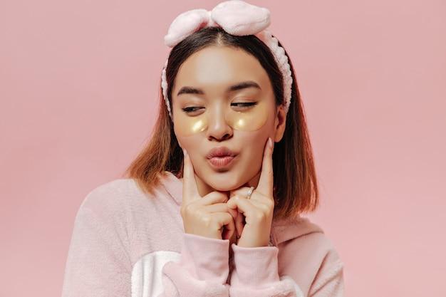 Mulher bonita morena de pijama macio e bandana mandando beijo e poses com tapa-olhos na parede rosa isolada