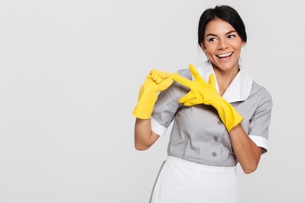 Mulher bonita morena de uniforme cinza, tirando as luvas protetoras amarelas enquanto sorrindo e olhando de lado