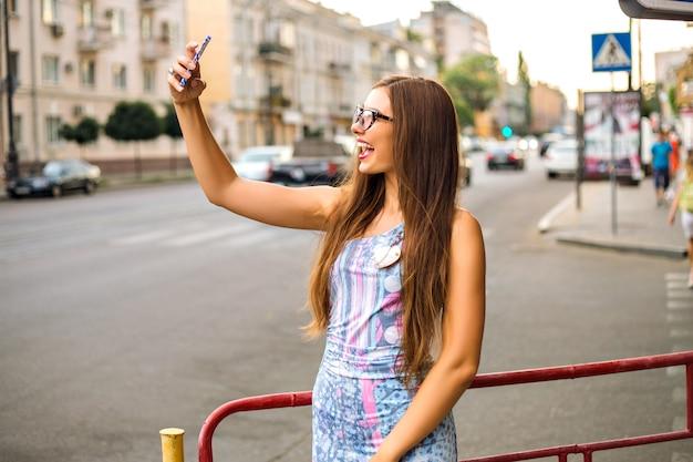 Mulher bonita morena fazendo selfie na rua.