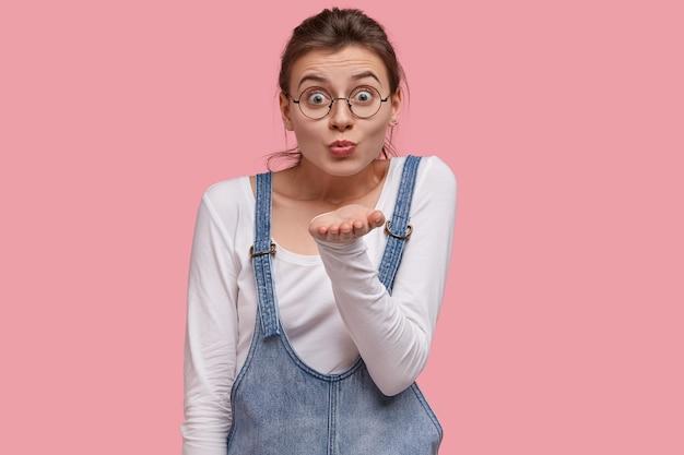 Mulher bonita mostra sinal de beijo no ar, estica a palma da mão perto da boca, faz careta, usa óculos redondos, suéter branco e sarafan jeans