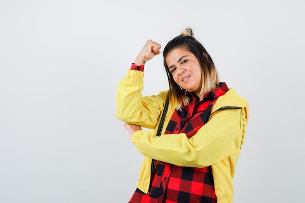 Mulher bonita mostrando os músculos do braço na camisa, jaqueta e parecendo confiante. vista frontal.