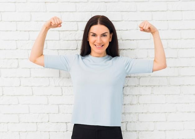 Mulher bonita mostrando os músculos do braço sorrindo