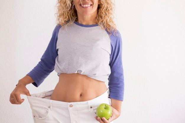 Mulher bonita mostrando sua velha pantalona grande depois de perder peso em casa - fazer exercícios em casa e trabalhar para ficar melhor consigo mesma - comendo bem com uma maçã na mão