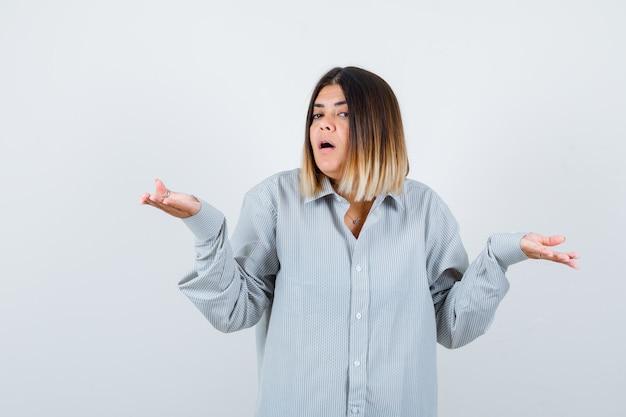 Mulher bonita mostrando um gesto impotente na camisa e olhando perplexo, vista frontal.