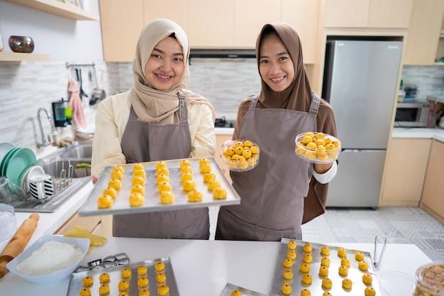 Mulher bonita muçulmana asiática com hijab fazendo bolo de nastar. bandeja cheia de petisco caseiro