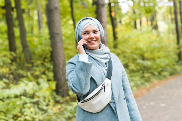 Mulher bonita muçulmana fala no telefone no parque.