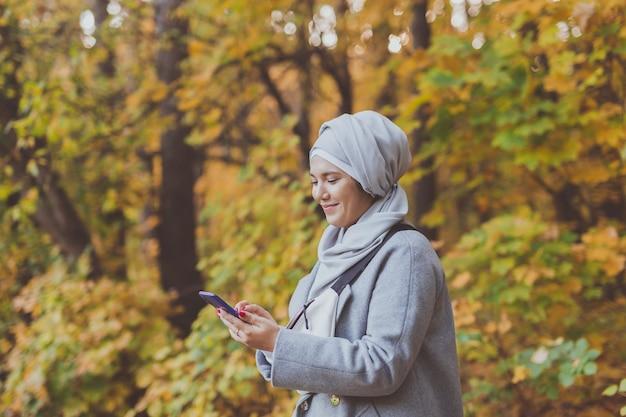 Mulher bonita muçulmana usando telefone celular ao ar livre. mulher árabe usando hijab usando o smartphone. menina islâmica enviando mensagens de texto com um telefone de mensagem no parque da cidade. copie o espaço