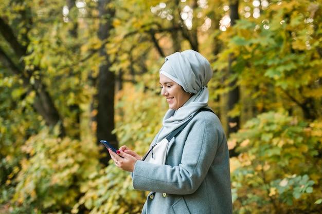 Mulher bonita muçulmana usando telefone celular ao ar livre mulher árabe usando hijab usando smartphone islâmico
