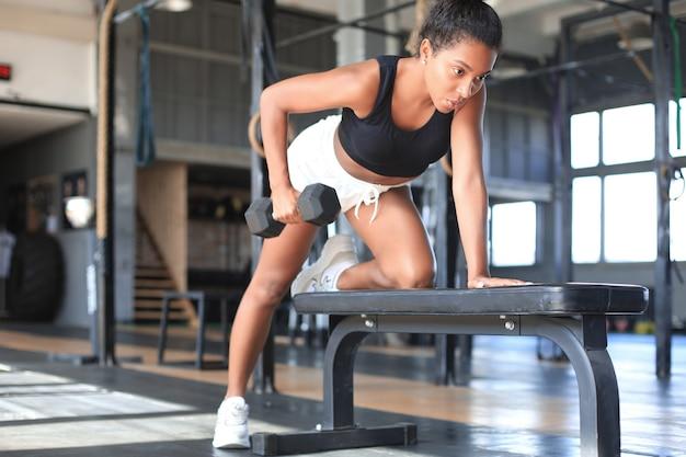 Mulher bonita muscular em forma que exercita os músculos do edifício.