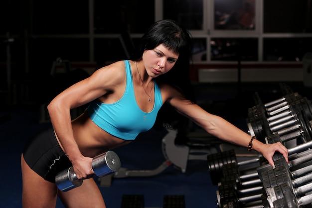Mulher bonita muscular em uma academia