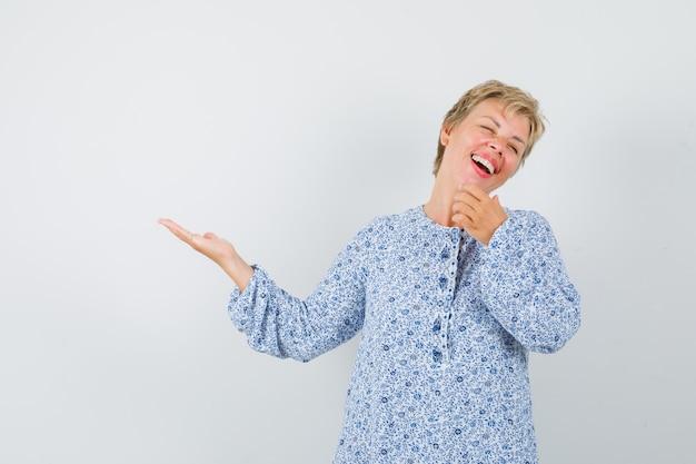 Mulher bonita na blusa estampada, apontando para alguém enquanto ri e olha alegre, vista frontal.