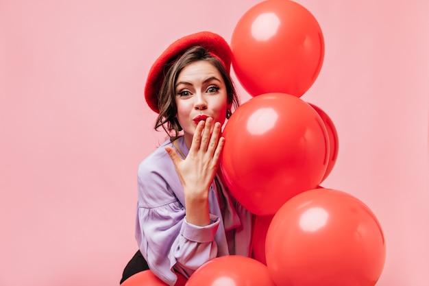 Mulher bonita na blusa lilás e boina vermelha sopra beijo e segura balões no fundo rosa.