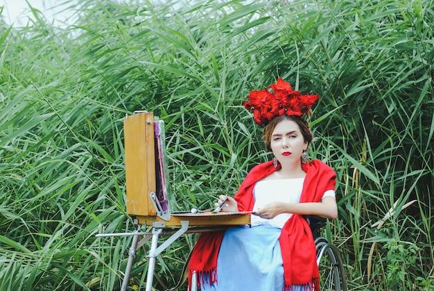 Mulher bonita na cadeira de roda, pintando.