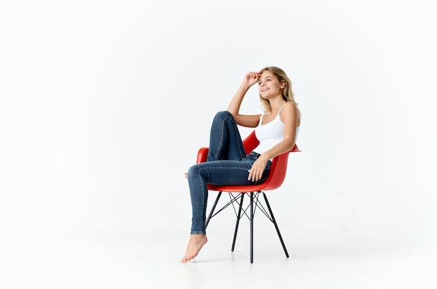 Mulher bonita na cadeira vermelha posando fashion estilo de vida