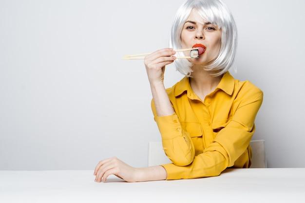 Mulher bonita na camisa amarela peruca branca sushi rola comendo. foto de alta qualidade
