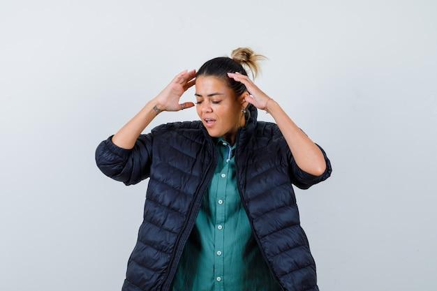 Mulher bonita na camisa verde, jaqueta preta com as mãos nas têmporas e parecendo irritada, vista frontal.