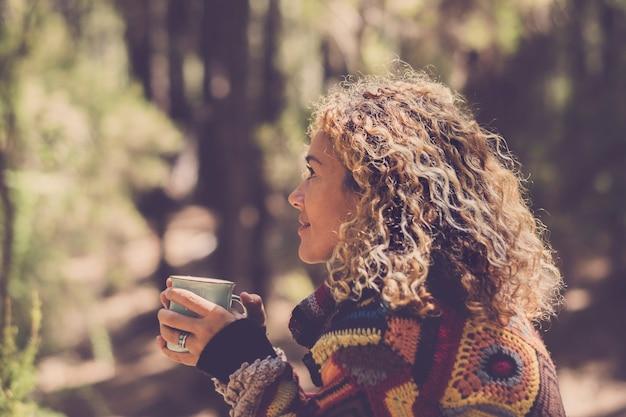 Mulher bonita na floresta de outono, apreciando a sensação com a natureza com um suéter quente - senhora senta-se com árvores em nackground em uma floresta e segura um copo com uma bebida quente nas mãos. viagem de menina e