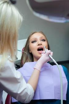 Mulher bonita na inspeção dos dentes em odontologia