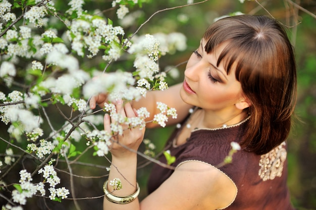 Mulher bonita na natureza perto de árvores floridas