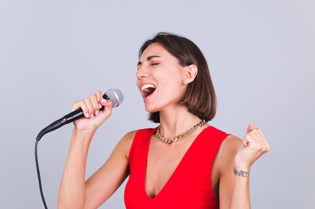 Mulher bonita na parede cinza com microfone cantando a música favorita emocional feliz positivo alegre