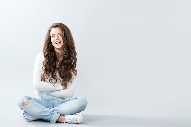 Mulher bonita na parede vazia sorrindo e sentada no chão