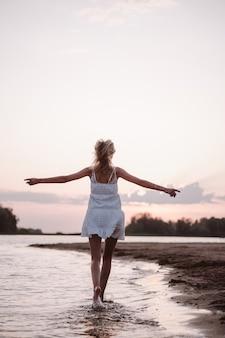 Mulher bonita na parte traseira da praia, uma jovem loira esguia em um vestido branco está girando e ...