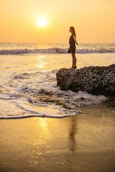 Mulher bonita na praia ao pôr do sol