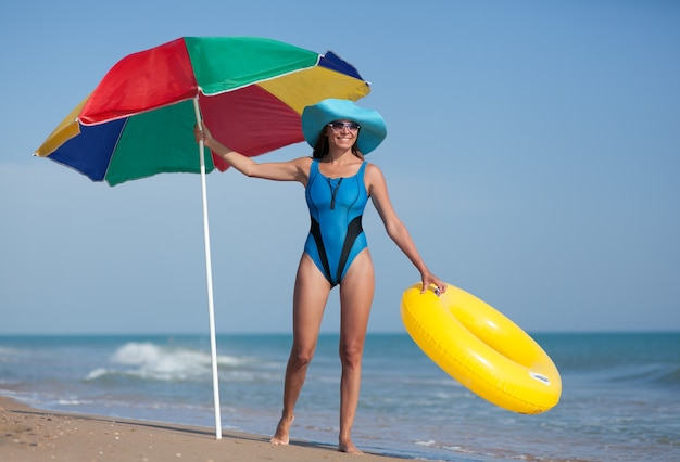 Mulher bonita na praia de areia do mar sob o céu azul