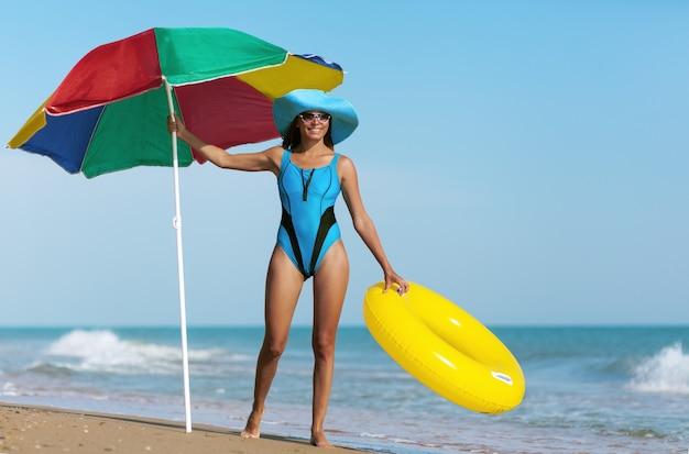 Mulher bonita na praia do mar sob o céu azul