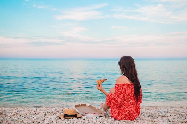Mulher bonita na praia fazendo piquenique com pizza