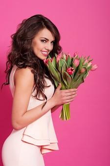 Mulher bonita na primavera com buquê de tulipas cor de rosa
