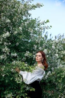 Mulher bonita na primavera nos ramos de arbustos floridos de macieira