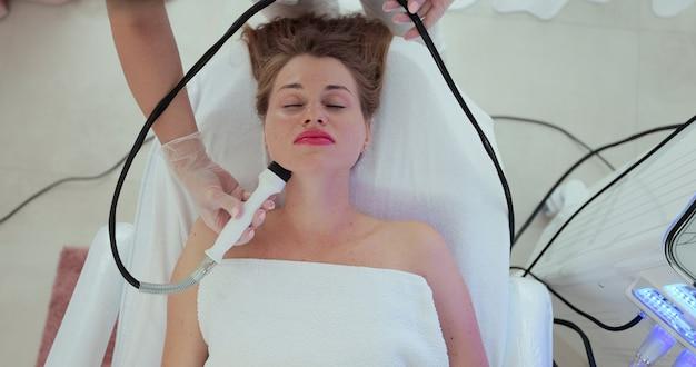 Mulher bonita na recepção de um cosmetologista recebe uma massagem a vácuo da pele do rosto usando um dispositivo cosmetológico. cosmetologia e conceito de spa.