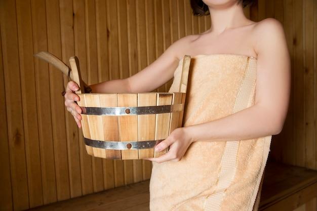 Mulher bonita na sauna, acessórios de banho. balde de madeira e varas