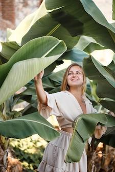 Mulher bonita na selva. um resort ou hotel com árvores e plantas tropicais. mulher com folha de bananeira perto. garota de férias na floresta tropical