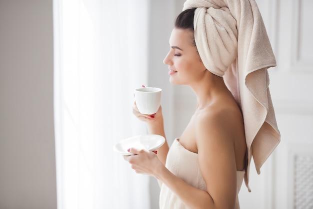 Mulher bonita na toalha depois do banho, bebendo café da manhã