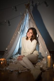 Mulher bonita na véspera de natal sentada em um interior confortável