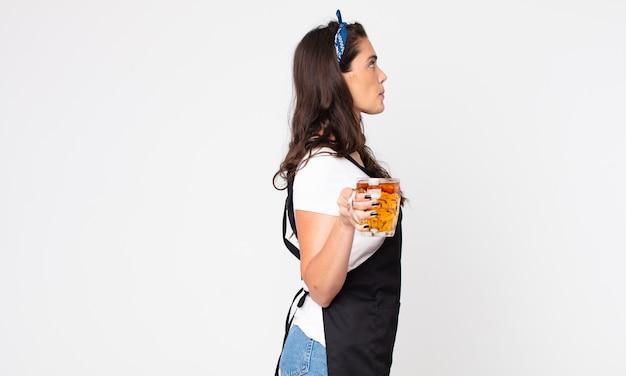 Mulher bonita na vista de perfil pensando, imaginando ou sonhando acordada e segurando um copo de cerveja