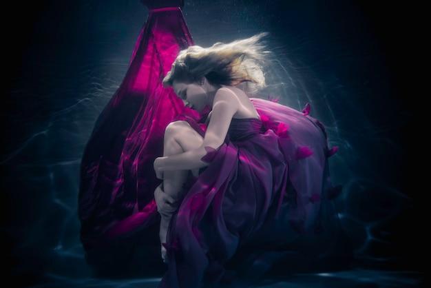 Mulher bonita nadando com vestido extravagante debaixo d'água