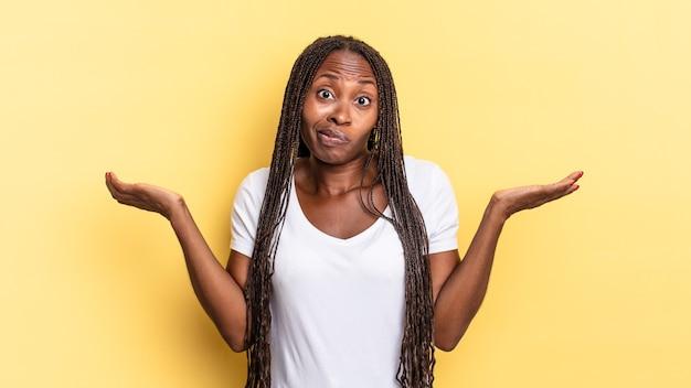 Mulher bonita negra afro se sentindo perplexa e confusa, duvidando, ponderando ou escolhendo opções diferentes com expressão engraçada