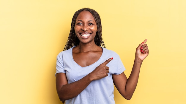 Mulher bonita negra afro sorrindo alegremente e apontando para o lado e para cima com as duas mãos mostrando o objeto no espaço da cópia