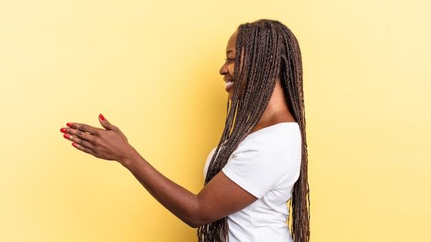 Mulher bonita negra afro sorrindo, cumprimentando você e oferecendo um aperto de mão para fechar um negócio de sucesso, conceito de cooperação