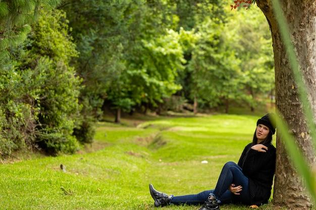 Mulher bonita no boné de inverno em dia nublado, sentado no gramado no parque ao lado de uma árvore
