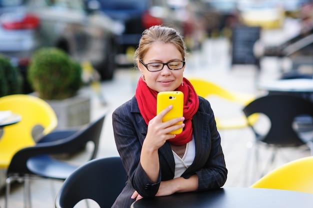 Mulher bonita no café com smartphone