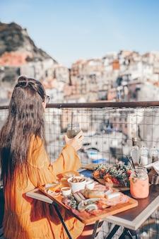Mulher bonita no café da manhã no café ao ar livre com uma vista incrível em cinque terre