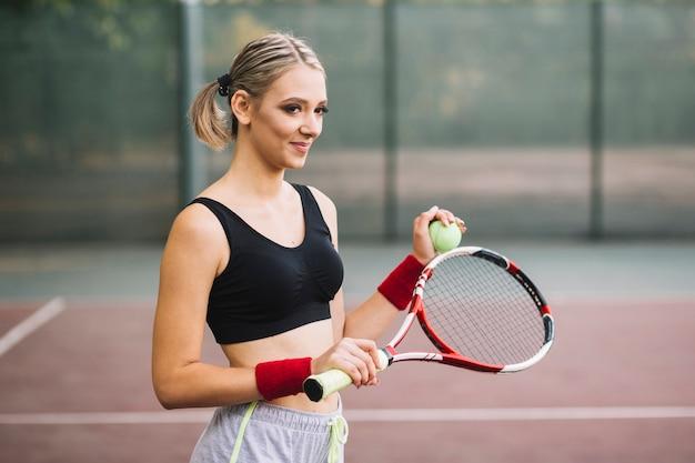 Mulher bonita no campo de tênis jogando