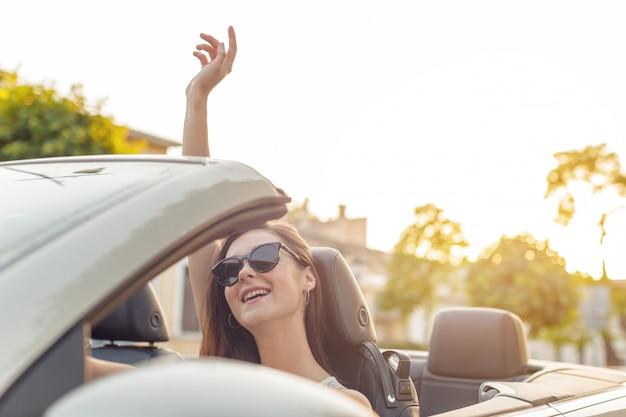 Mulher bonita no carro conversível em um dia ensolarado em uma cidade