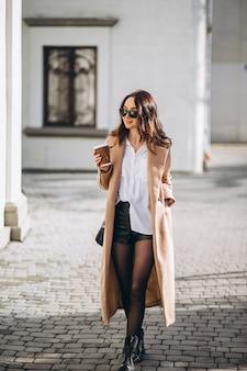 Mulher bonita no casaco bebendo café lá fora na rua