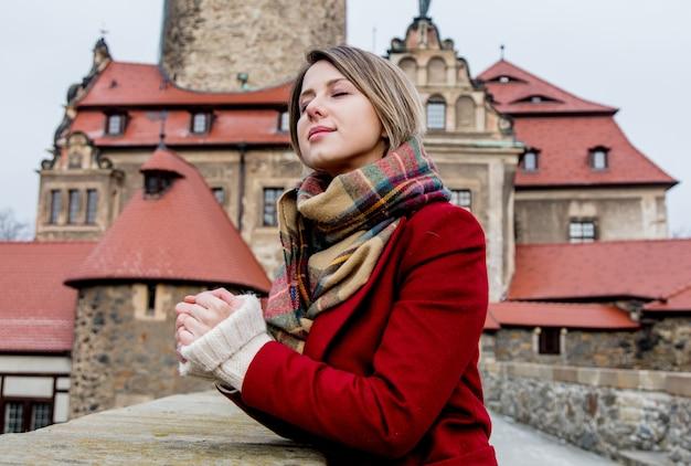 Mulher bonita no casaco vermelho fica perto do castelo