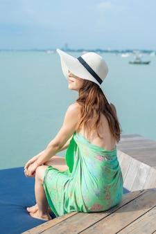 Mulher bonita no chapéu branco está sentado no hotel com a praia